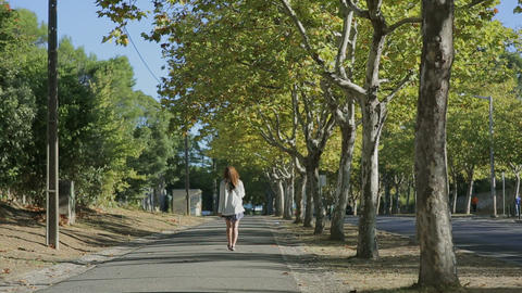 Girl walking throught cork tree alley street portugal Footage