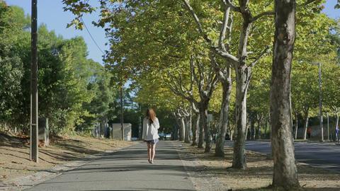 Girl walking throught cork tree alley street portugal Footage
