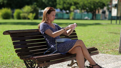 Young beautiful woman make selfy holding mobile phone in hand and sitting on the Footage