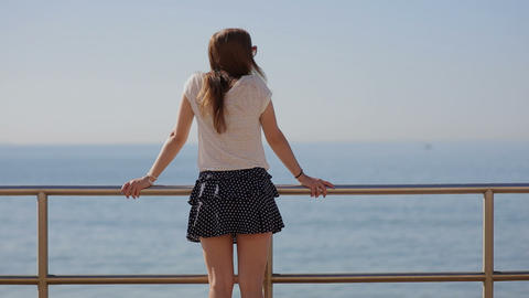 Rear view of a thoughtful beautiful young woman in blue skirt contemplating the  Footage