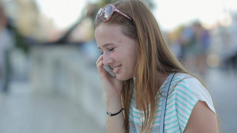 Happy girl talking by smart phone in a city embankment sitting Footage