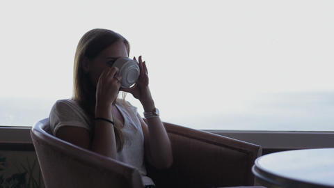 young beautiful girl sits in a cafe with beautiful panoramic views of atlantic o Footage
