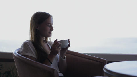 young beautiful girl sits in a cafe beholding beautiful... Stock Video Footage
