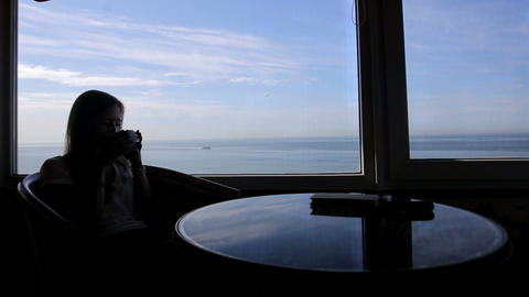 Long Shot Of Silhouette Of Young Beautiful Girl Sits In A Cafe With Panoramic Vi stock footage