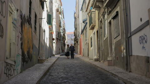 Together in an old street, old couple walking throught Lisbon street Footage