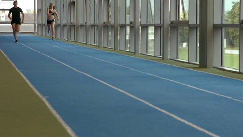 Couple racing on indoor track Footage