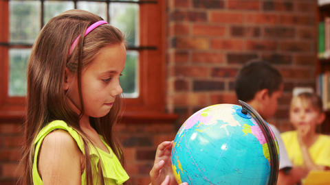 Little girl looking at globe in library Footage