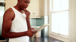 Man using his tablet at breakfast in kitchen Footage