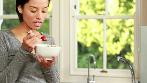 Woman eating cereal in kitchen Footage