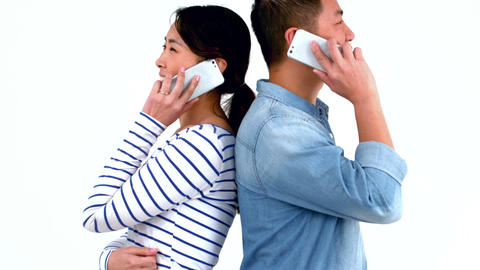 Smiling couple having phone calls back to back Footage