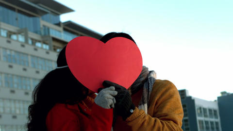 Romantic couple hiding themselves behind heart shape Footage