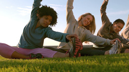 Smiling sporty women stretching during fitness class Live Action