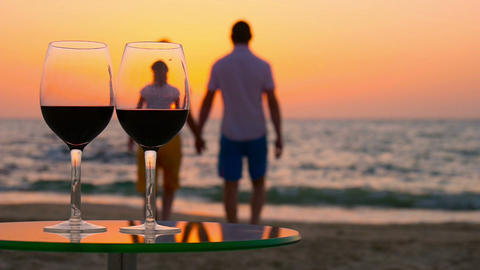 Glasses of wine on the table. In the background, a couple goes out to sea Footage