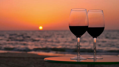 Glasses of red wine on a table against the sea Footage