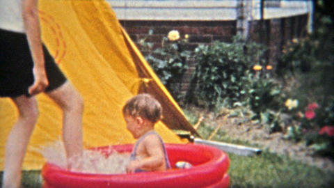 1954: Brother splashing baby boy in kiddie backyard fun pool Footage