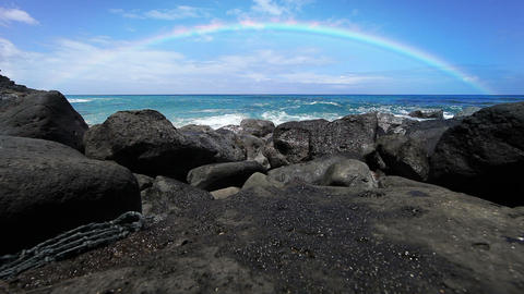 Rainbow over a beach with lava rocks in Hawaii Footage