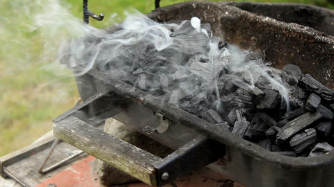 Smoke rising from charcoal placed in grill - close up Live Action