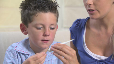 Mother taking sons temperature with thermometer and... Stock Video Footage