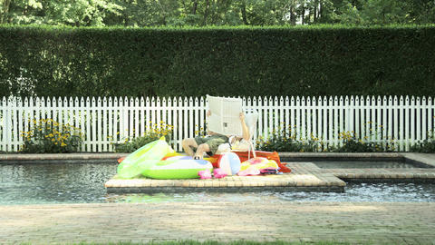 Man relaxing by swimming pool with newspaper and inflatables Stock Video Footage