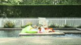 Man relaxing by swimming pool with newspaper and inflatables Footage