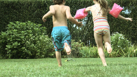 Boy and girl jumping through water from garden sprinkler Stock Video Footage