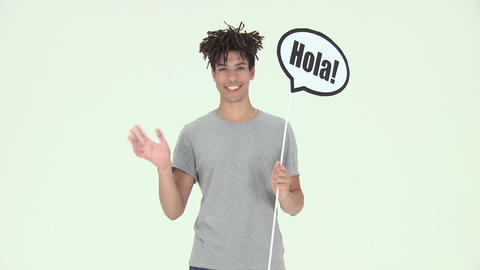 Young man holding sign that reads hola and waving Stock Video Footage