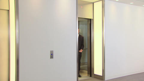 Businessmen come out of elevator, businesswoman goes into... Stock Video Footage