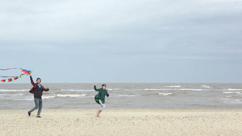 Couple by sea with kite, running past camera Stock Video Footage