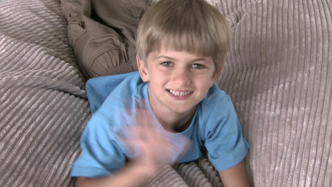 Boy jumping on beanbag and waving at camera Stock Video Footage