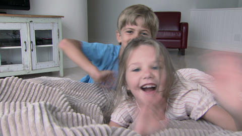 Boy and girl running and jumping onto beanbag, smiling... Stock Video Footage