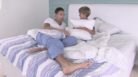 Father and son talking on bed, zoom in Stock Video Footage
