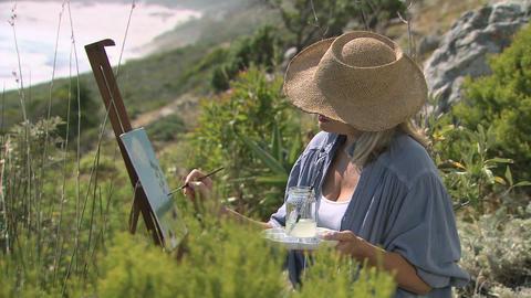 Artist painting on hillside Stock Video Footage