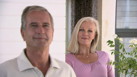 Couple looking at camera and smiling, camera changes focus from man to woman Footage