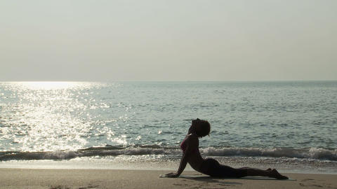 Woman practicing yoga on a beach Stock Video Footage
