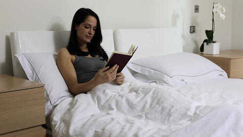 Young woman reading in bed Stock Video Footage