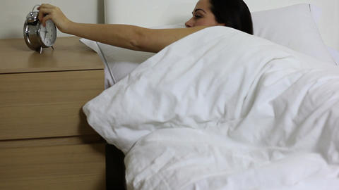 Woman in bed, turning off alarm and going back to sleep Stock Video Footage