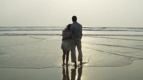 Couple standing in the sea as waves come in Live Action