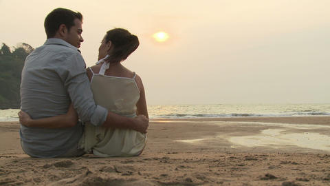 Couple sitting on beach at sunset Stock Video Footage