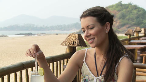 Woman at beach bar, talking to someone who is off camera Stock Video Footage