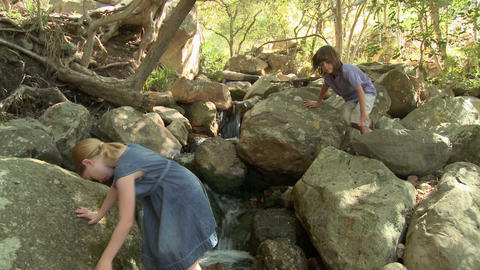 Boy and girl on walking on rocks by river Stock Video Footage