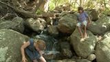 Boy and girl on walking on rocks by river Footage