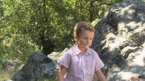 Boy walking by rocks with stick Stock Video Footage