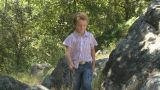Boy walking by rocks with stick Footage