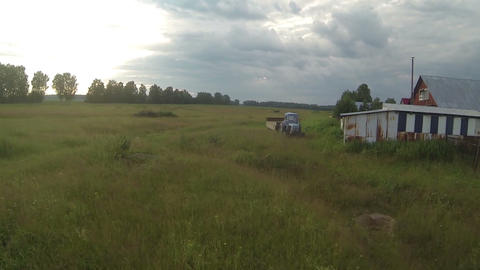 Old abandoned tractor in the field, storm is coming, country side russia. Aerial Footage