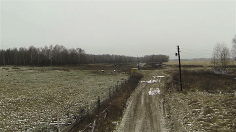 Aerial view of dirty road at farm in country side, russia first snow, autumn, ba Footage
