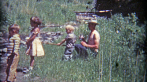 1961: Dad letting kids hold fishing pole on banks of the grassy river Footage