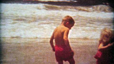 1961: Kids 1st time at beach boy scared of ocean waves Footage