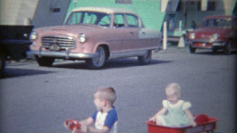1962: Kids in kiddie car and wagons pulled around trailer home park Footage