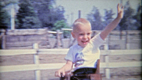 1962: Boys riding horses for 1st time smile and wave hello Footage