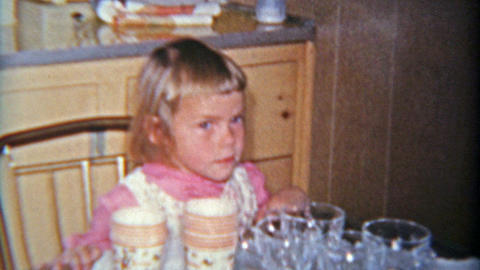1963: Grumpy jealous stonefaced sister at brothers 3 year old birthday party Footage